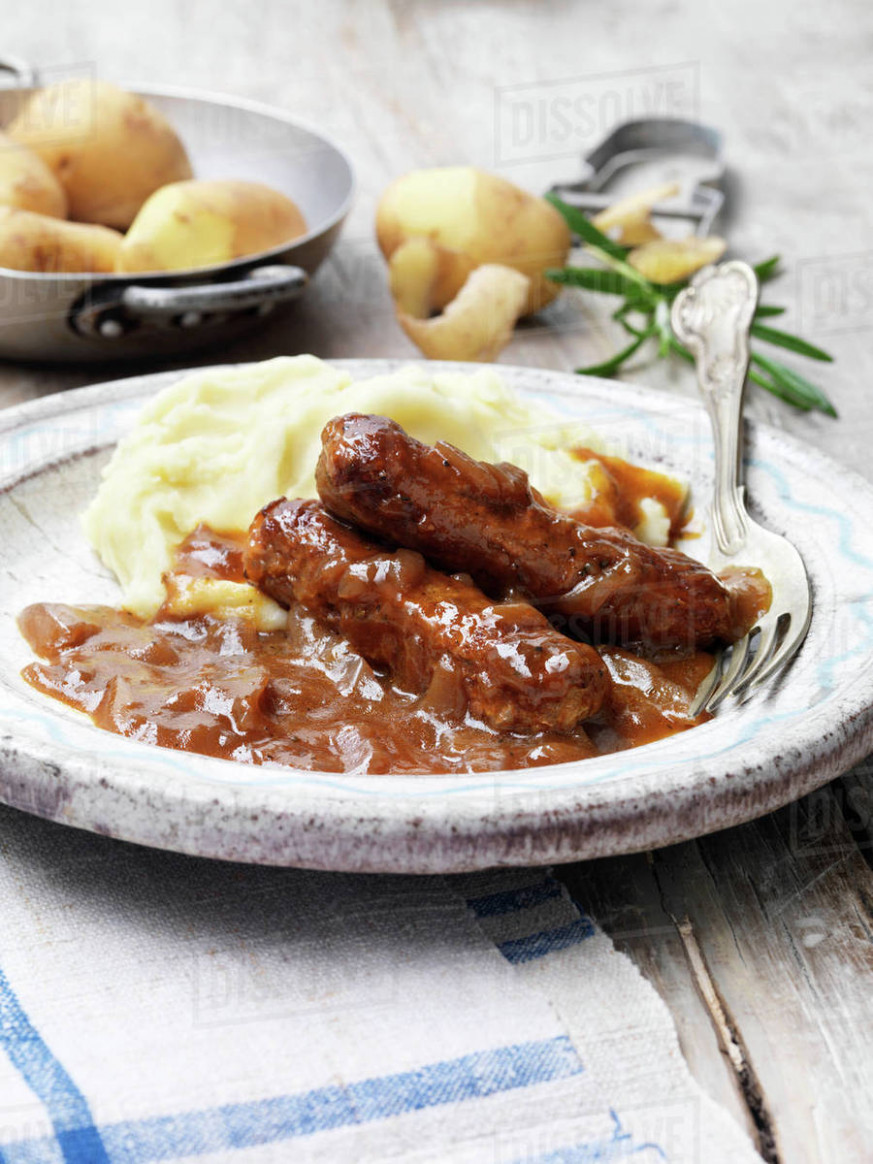 Food, vegetarian meals, vegetarian sausage and mash with onion gravy, peals  potatoes, rosemary, vintage bowl, rustic wooden table stock photo - recipe vegetarian onion gravy