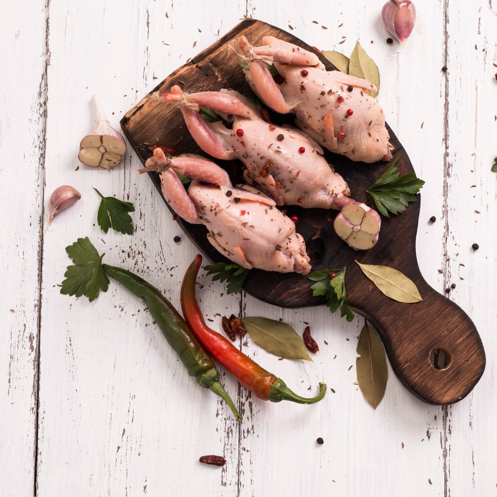 Fresh organic quails on vintage wooden table, healthy food - organic chicken recipes dinner