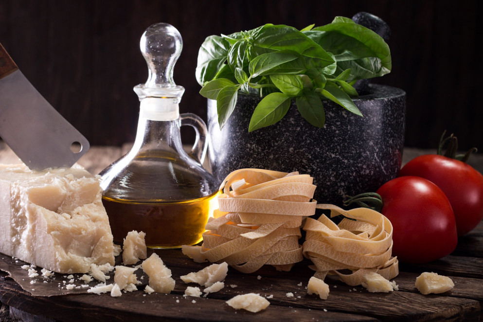 Italian and Mediterranean food ingredients on old wooden background pasta,olive oil, basil ,cheese,and mortar