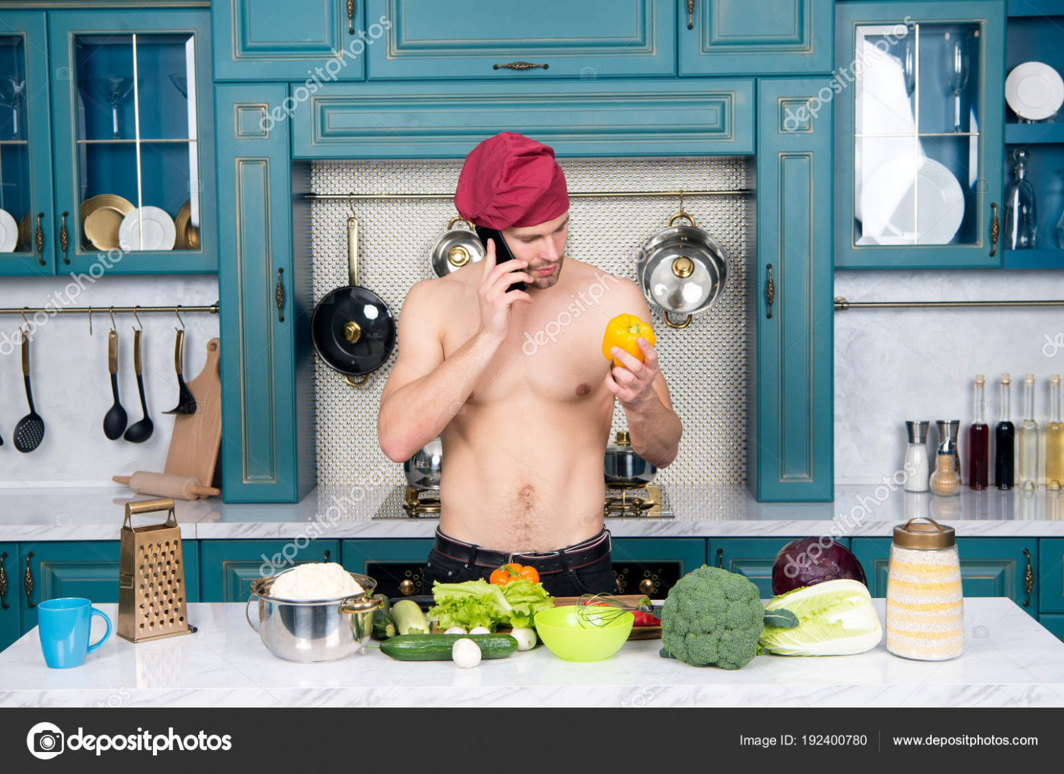 Macho cook with sexy torso talk on mobile phone in kitchen ..