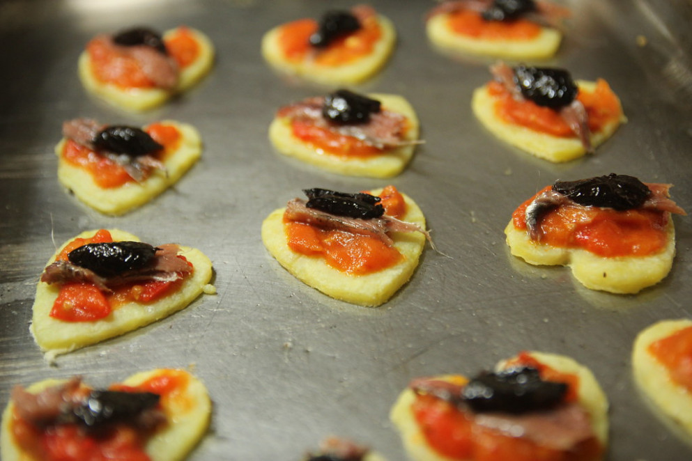Oven-ready. Heart-shaped potato canapés with spicy tomato and anchovies