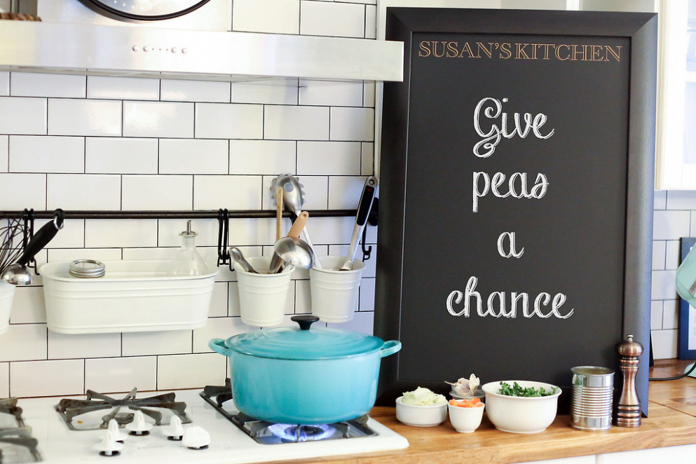 Personalized chalkboard on a kitchen counter next to Mediterranean vegetable pesto sauce ingredients next to a pot cooking on a stove - recipes spaghetti squash healthy